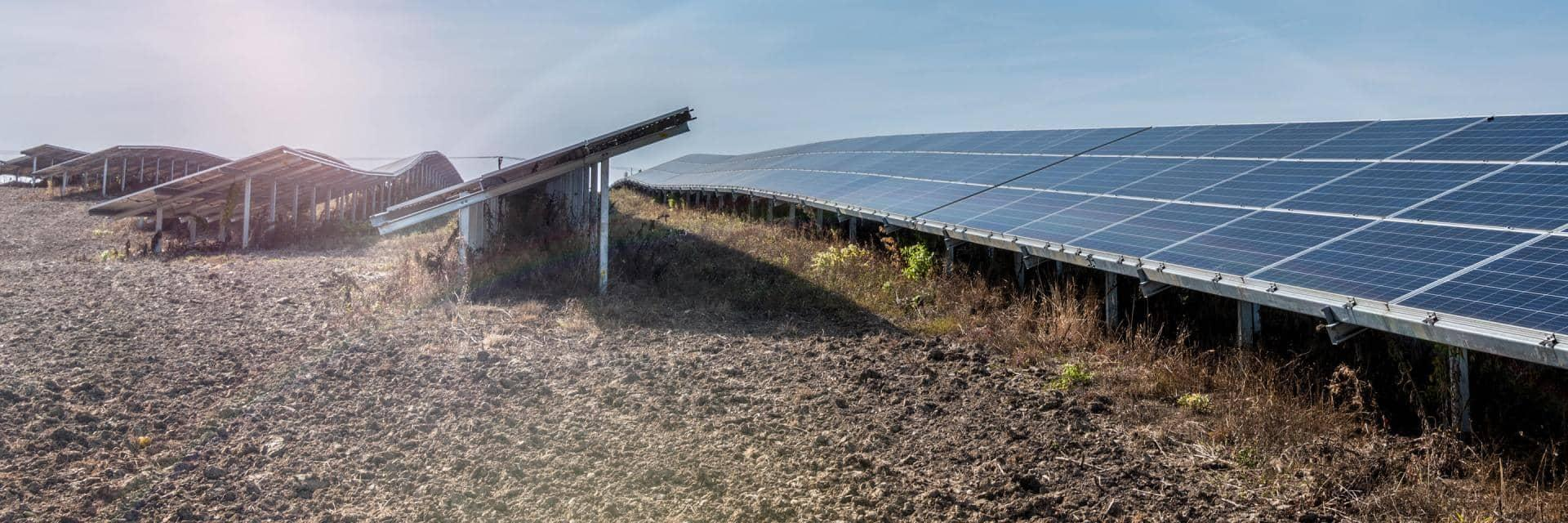 Five rows of large solar panels situated in a muddy field