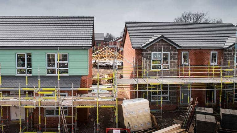 A row of houses covered with scaffolding.