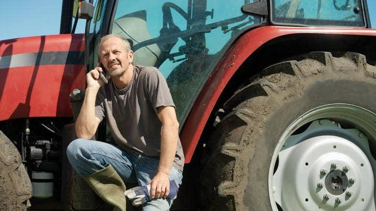 A farmer talks on his phone as he sits beside a muddy tractor