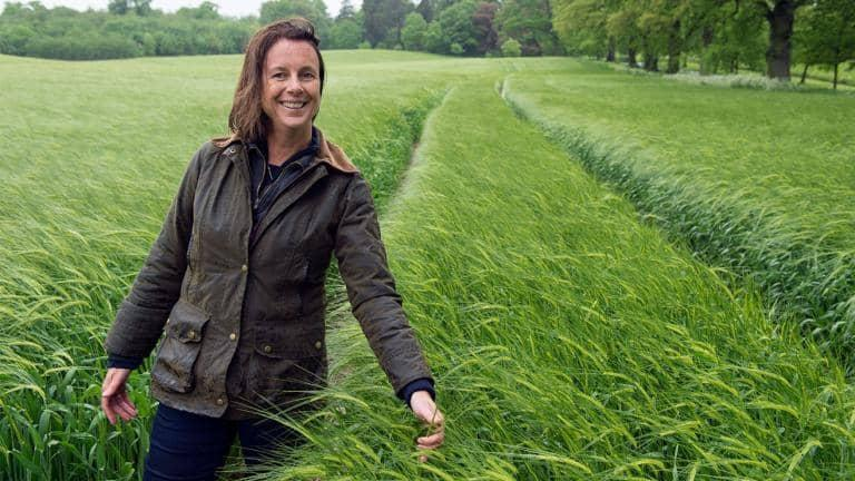 A farmer smiles as she walks through a field of crops wearing a wax jacket