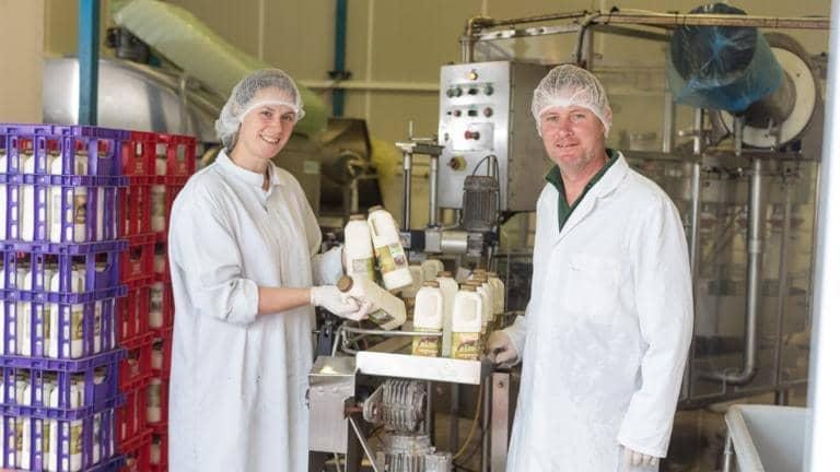 A woman and a man dressed in overalls hold up bottles of milk that have just come off the dairy production line