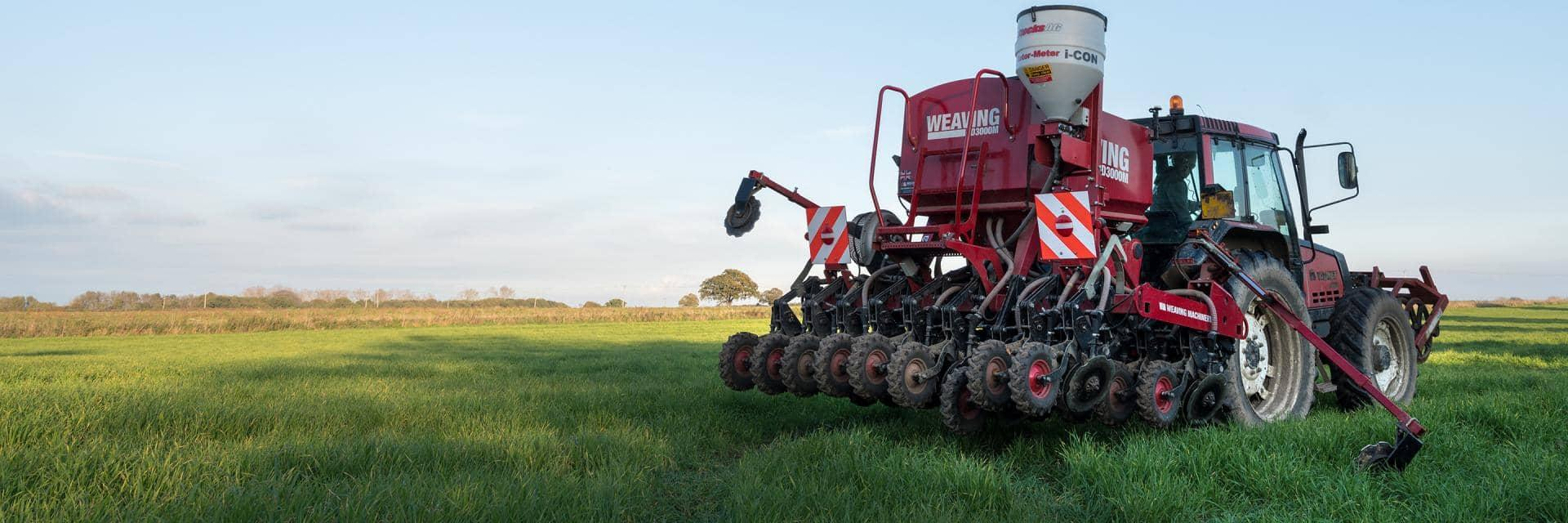 A large red agricultural vehicle being driven through a field of grass