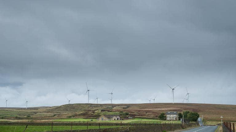 A line of wind turbines on a hillside with a road and old stone buildings in the foreground
