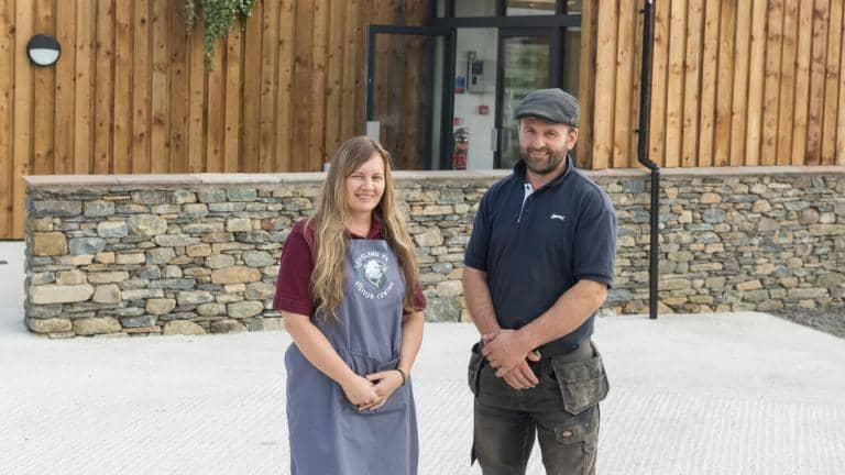 A woman and a man stand in front of a dry stone wall at the entrance to a farm visitor centre