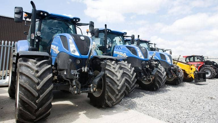 Four tractors and a digger parked side by side in an industrial site