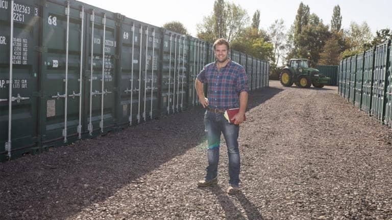 A man holding a diary stands outdoors between rows of container storage units with a tractor parked in the background