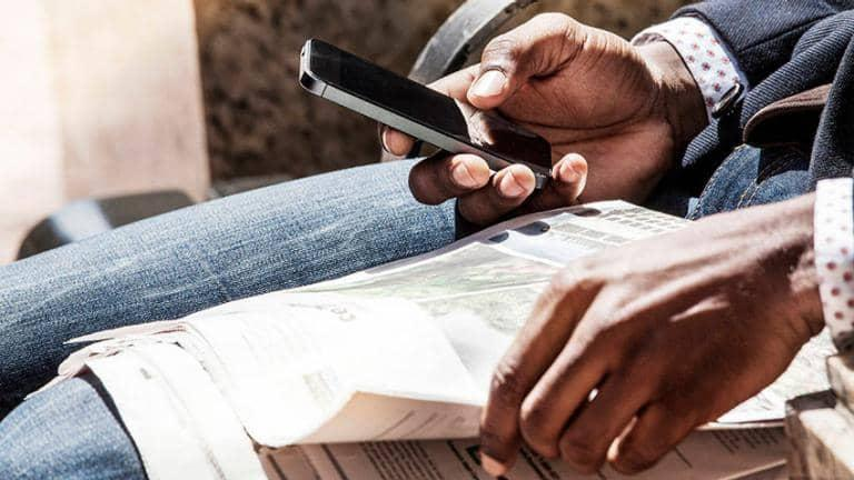 A person sitting with a newspaper on their lap looks at their smartphone