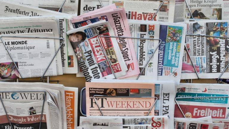 A selection of international newspapers displayed in metal racks on a wall