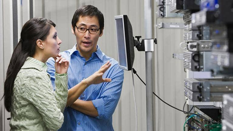 Two colleagues having a conversation in a server room.
