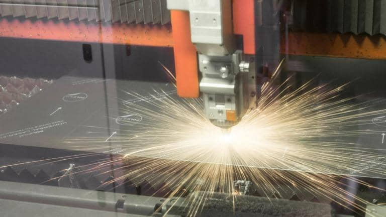 Machinery in a factory with sparks flying.