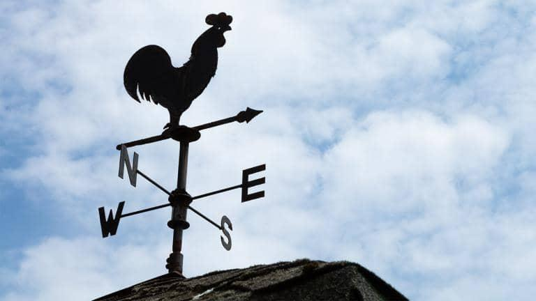 Weather vane with cockerel on a rooftop with a cloudy sky behind