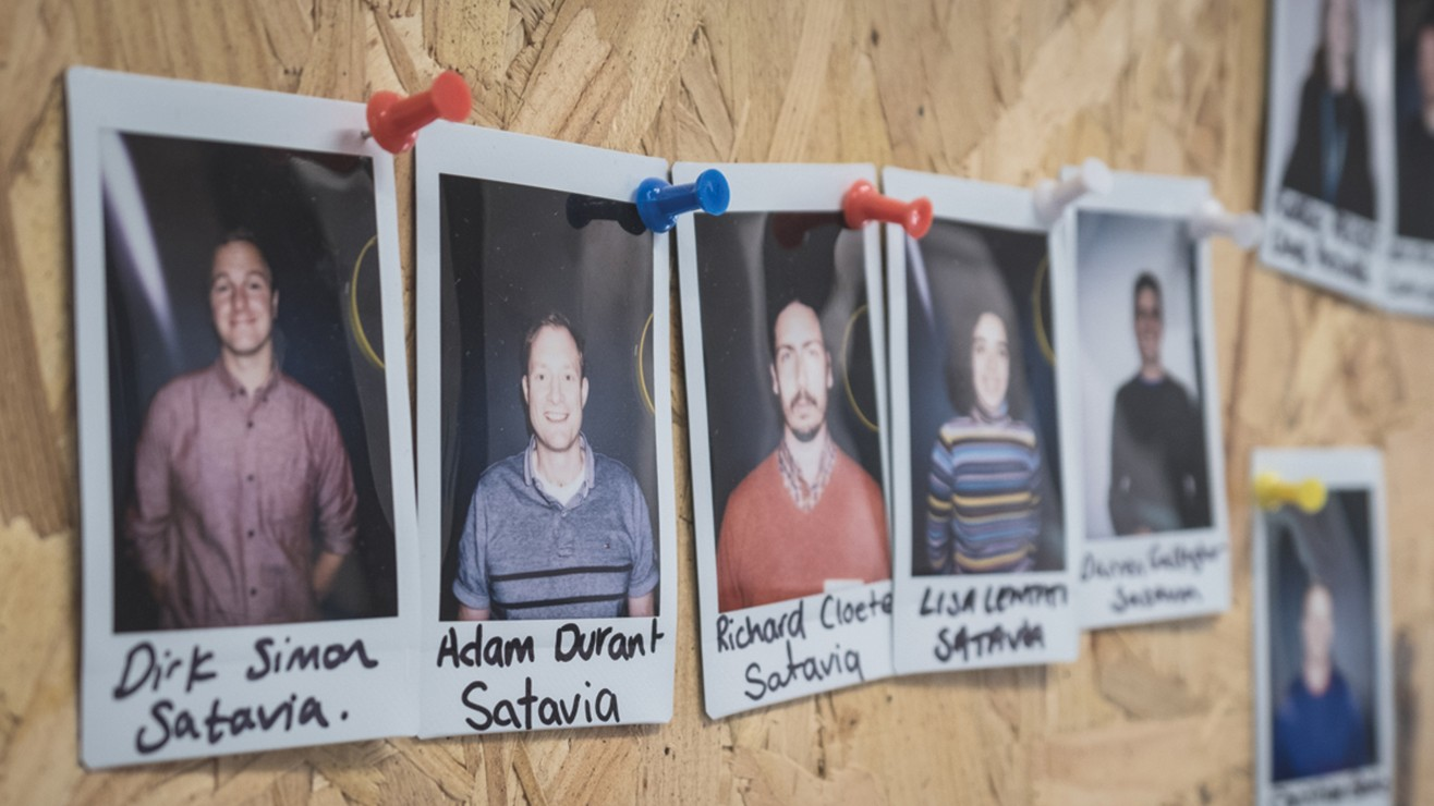 Polaroid photographs of members of staff pinned to a cork noticeboard