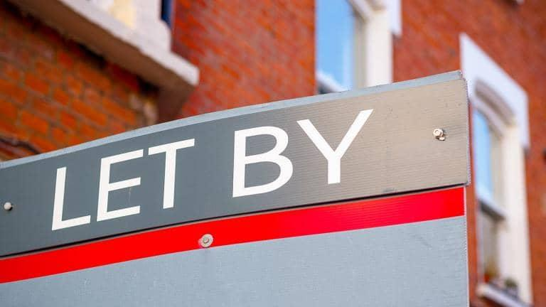A sign board outside a property that says 'let by'.