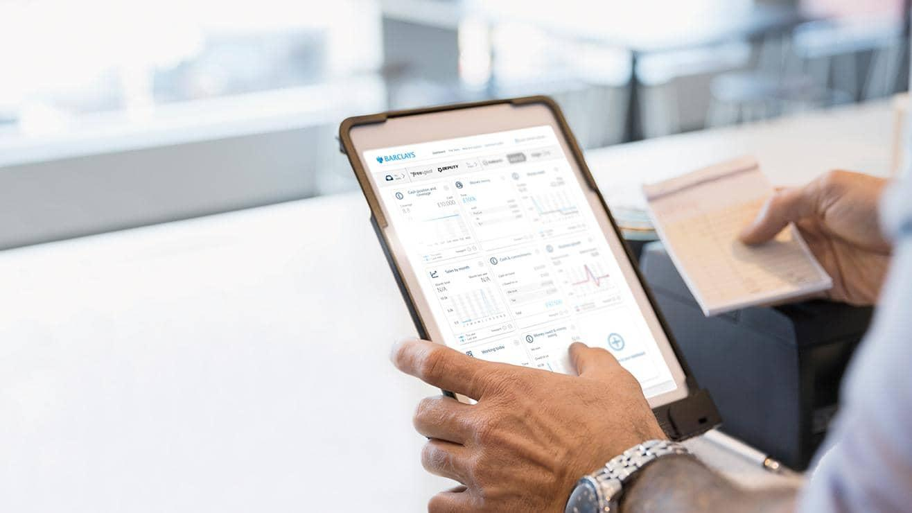 Hands holding a tablet which is displaying the Barclays SmartBusiness Dashboard