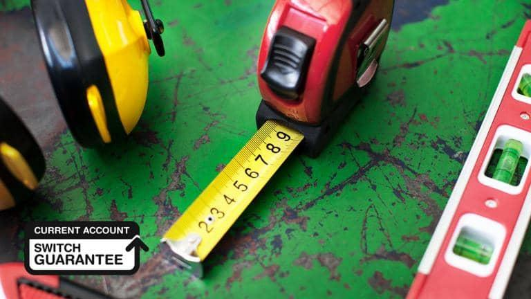Ear protectors, a tape measure and a spirit level arranged on a workbench