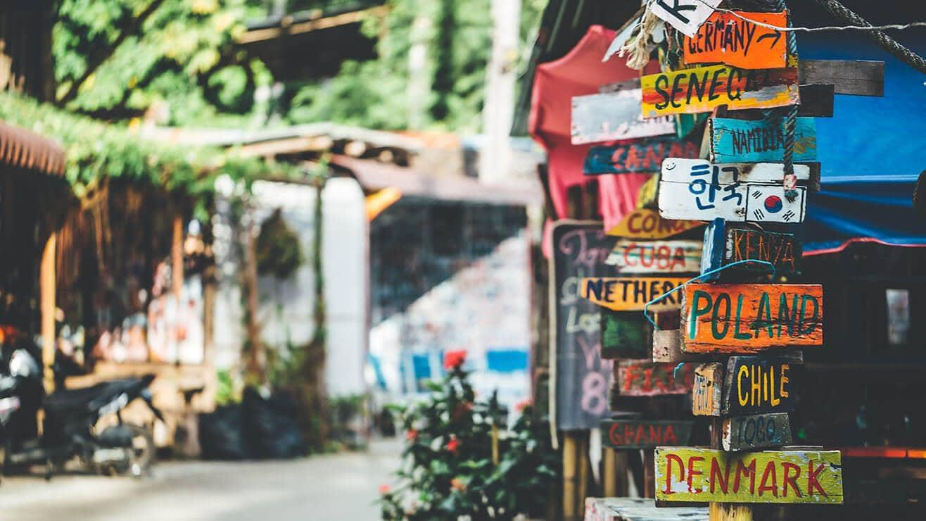 A sign post in an exotic location. The signs point to different countries around the world
