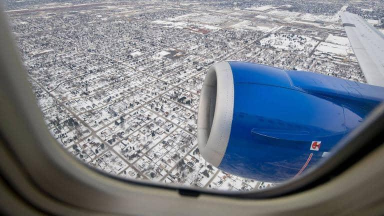 View out of the window of an airplane. The wing and ground below is visible