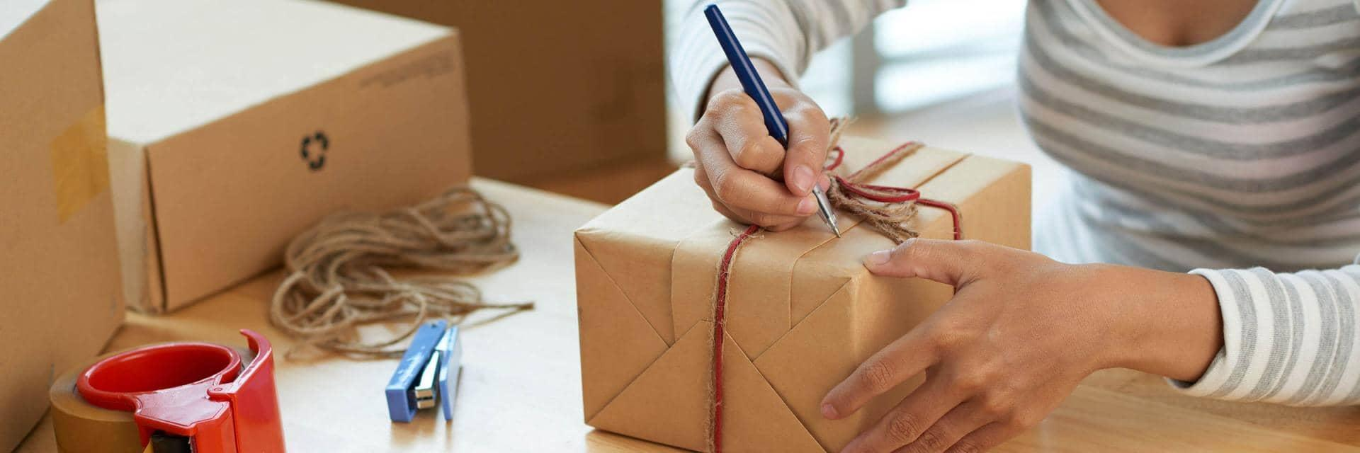 A woman writes an address on a hand wrapped brown paper parcel tied with string