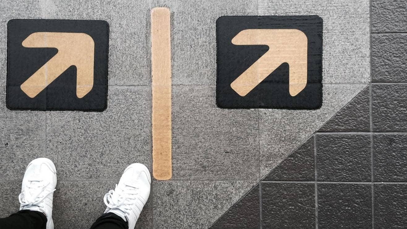 Feet wearing white trainers standing beside two arrows that are painted onto the ground