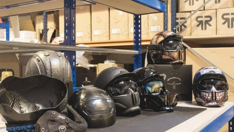 A selection of winter-sports helmets lined up on a shelf with cardboard boxes in the background