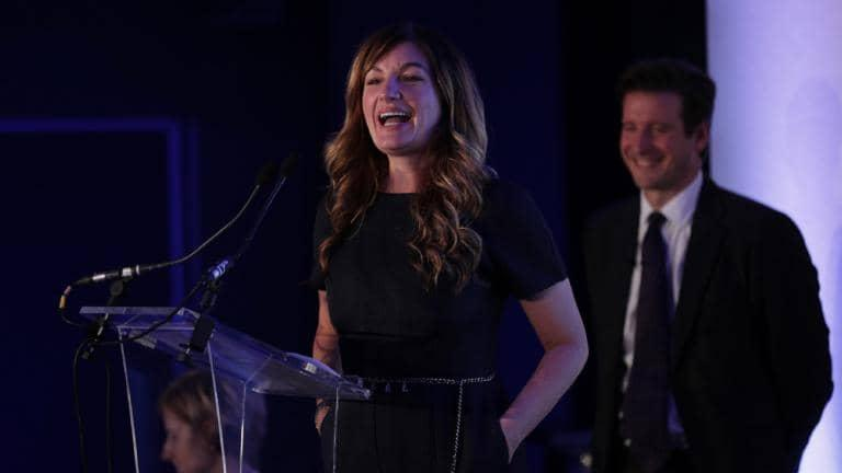 Baroness Karren Brady speaking into a microphone at a lectern, with a man standing behind her