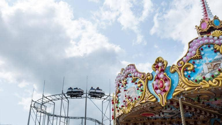 Close up on a section of a merry-go-round with a rollercoaster in the background