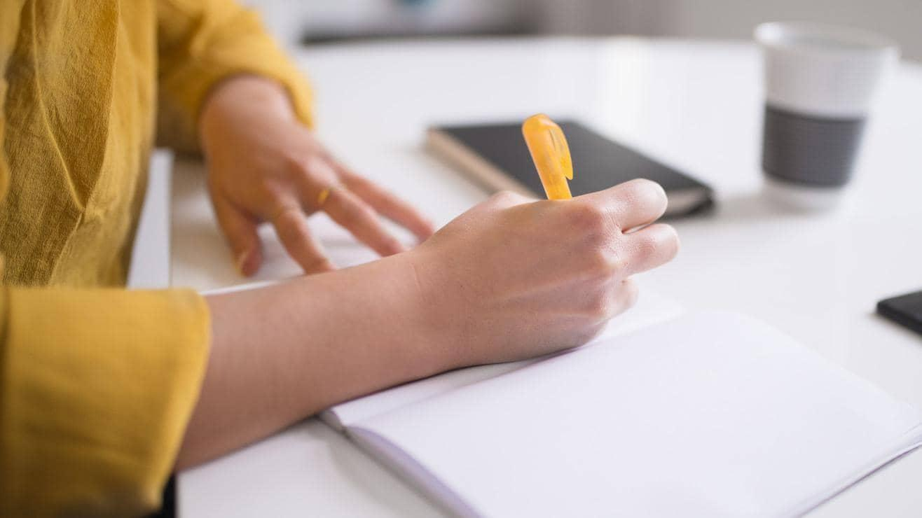 Woman writing in a blank notebook with a yellow pen