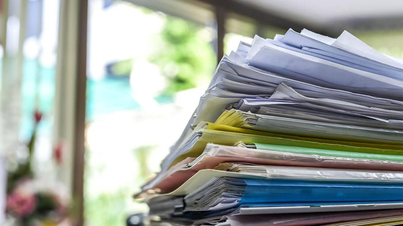 A stack of different coloured cardboard folders filled with paper files