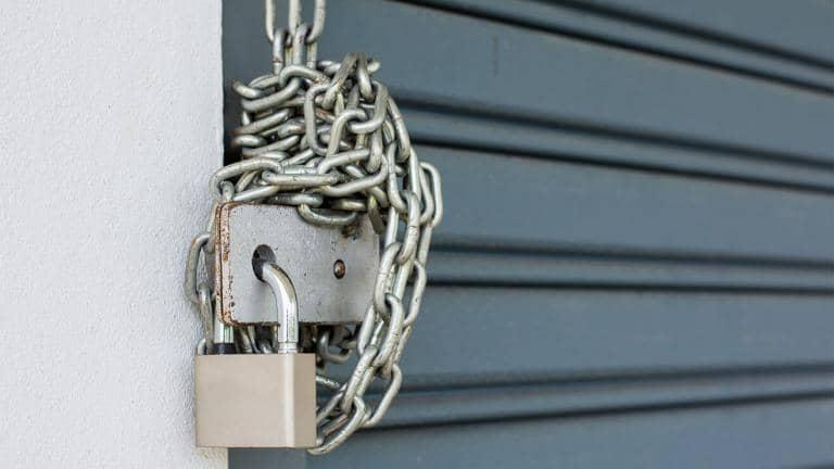 A padlock and chain securing a metal roller shutter