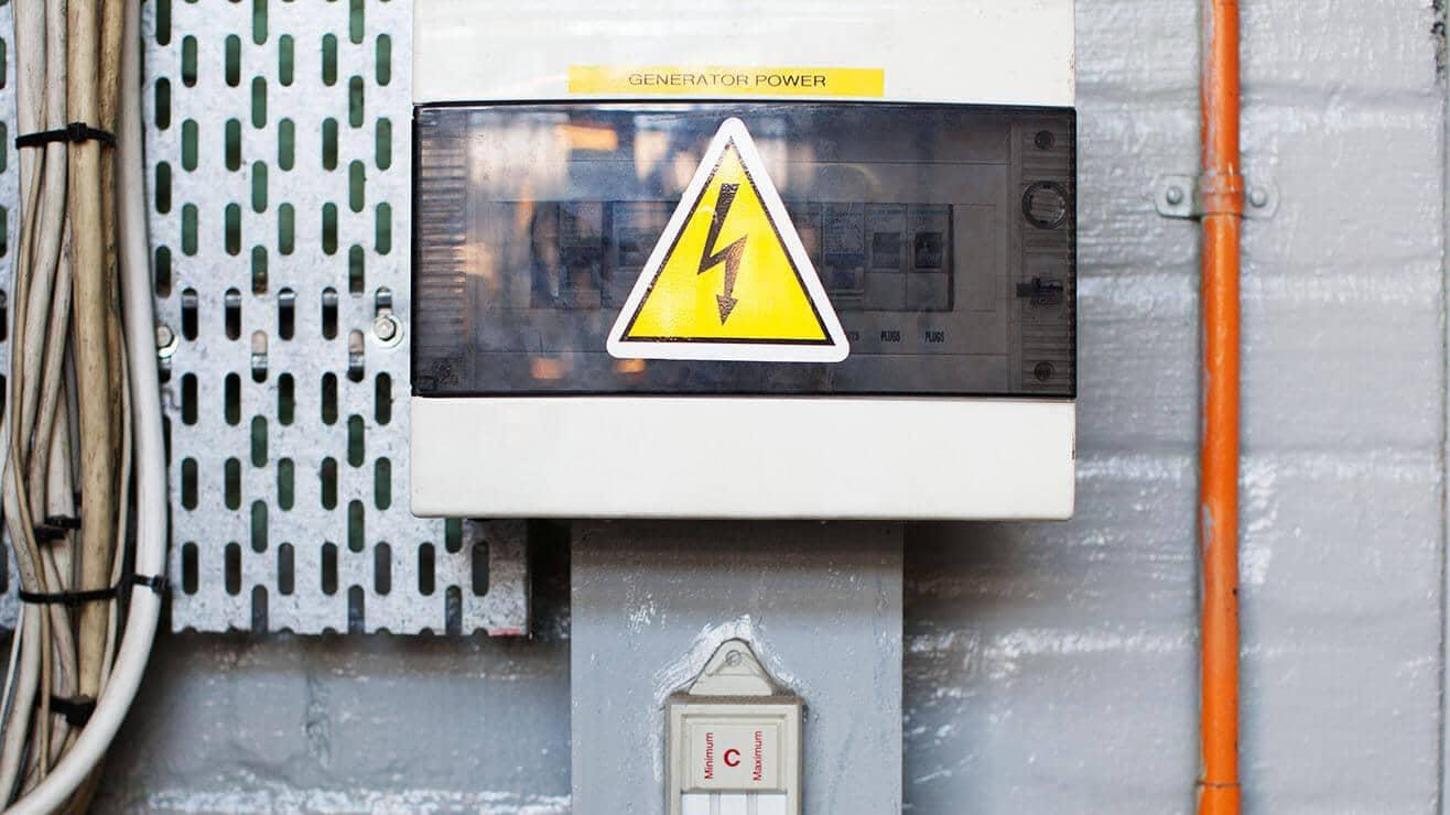Electrical fusebox with a large danger of electric shock sticker on the front