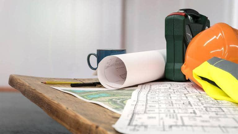 A reflective jacket, hardhat, rolled blueprint and mug placed on a wooden table