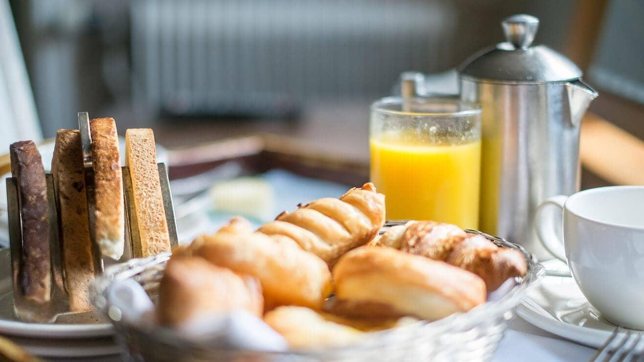 Various breakfast items, toast, orange juice, a pot of tea and a basket of pastries arranged on a table with a table cloth