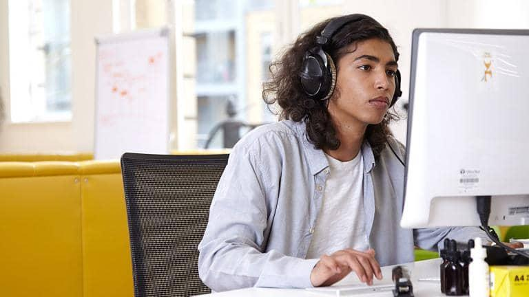 A man wearing headphones uses a computer in an office space
