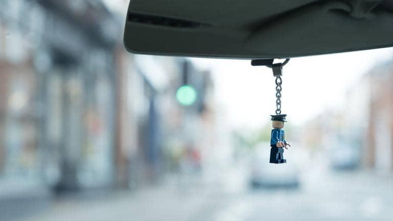 Keychain of a Lego policeman hanging from a car's rear view mirror