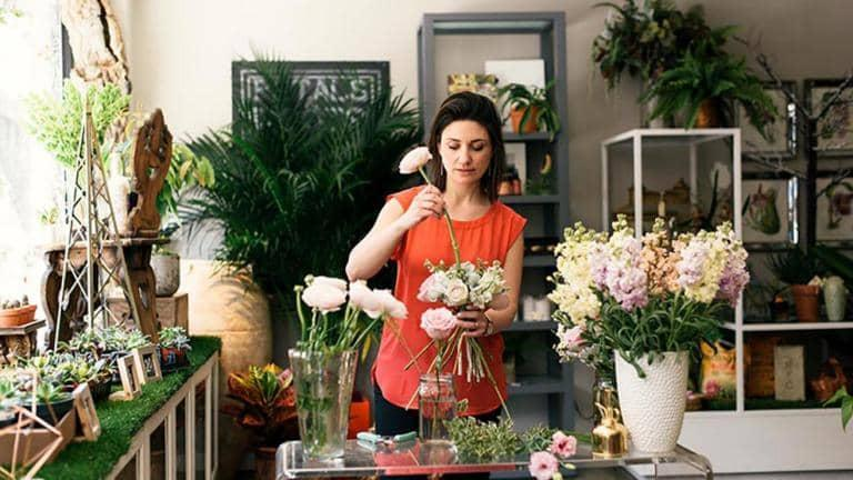 A woman is arranging flowers.