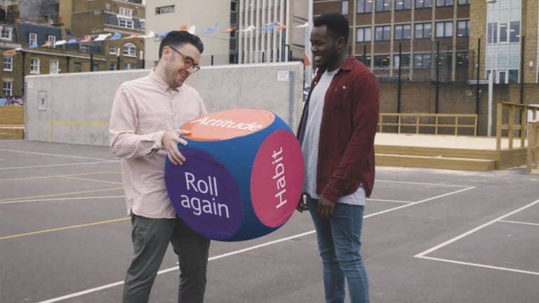 Two friends hold a giant dice with the word Attitude on its face