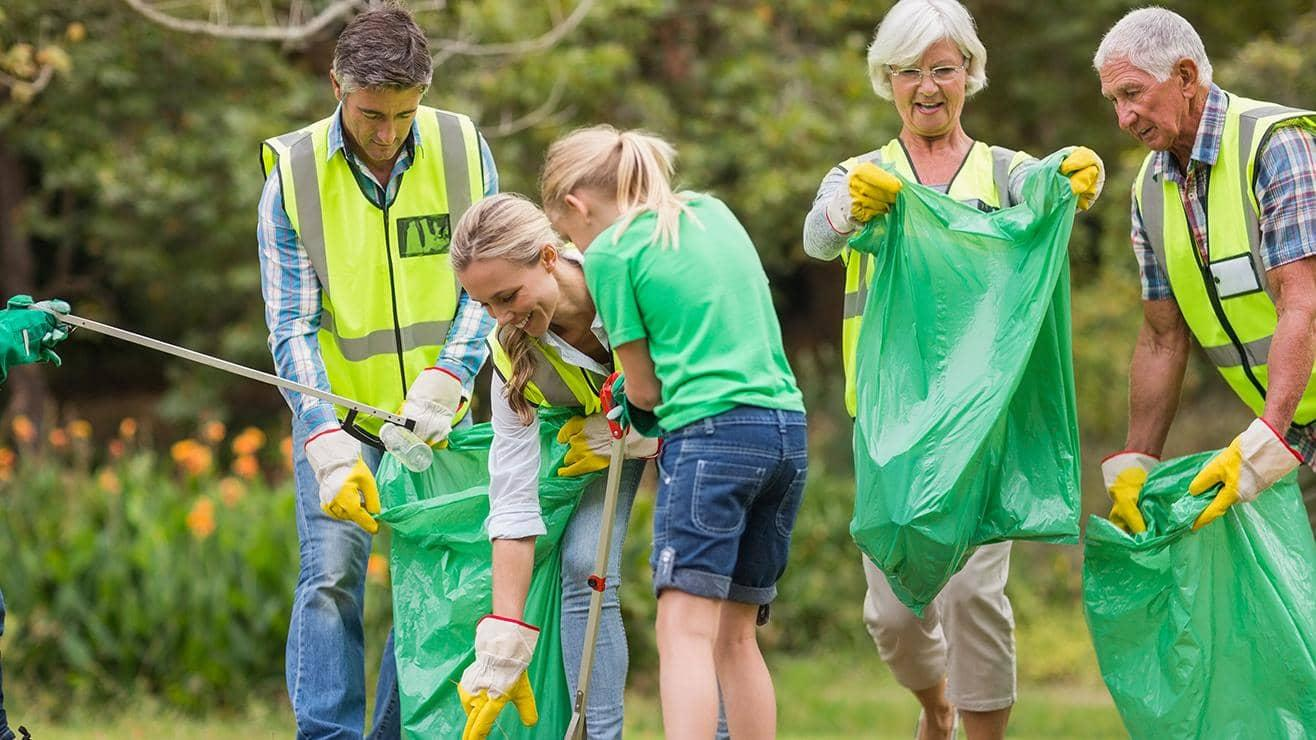 A group of people wearing gardening gloves pick up litter and put it in green bags
