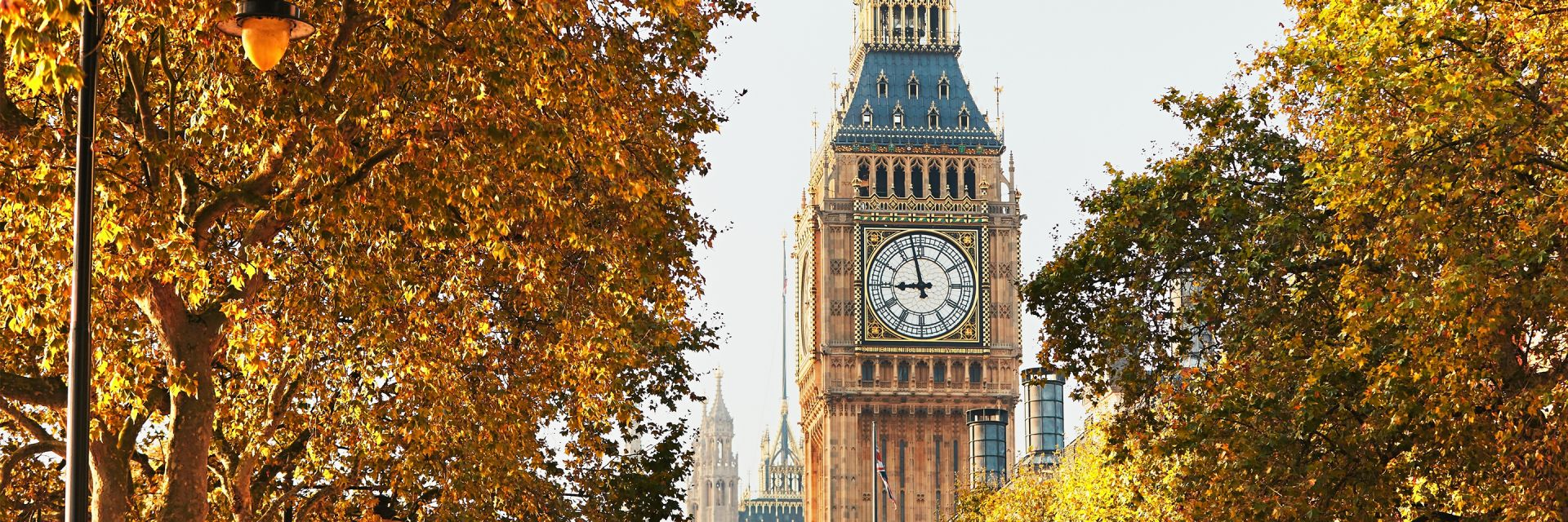 London's Big Ben surrounded by trees with orange leaves