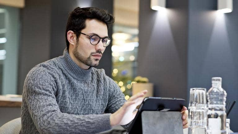 A man wearing glasses looks at a tablet at a dining table