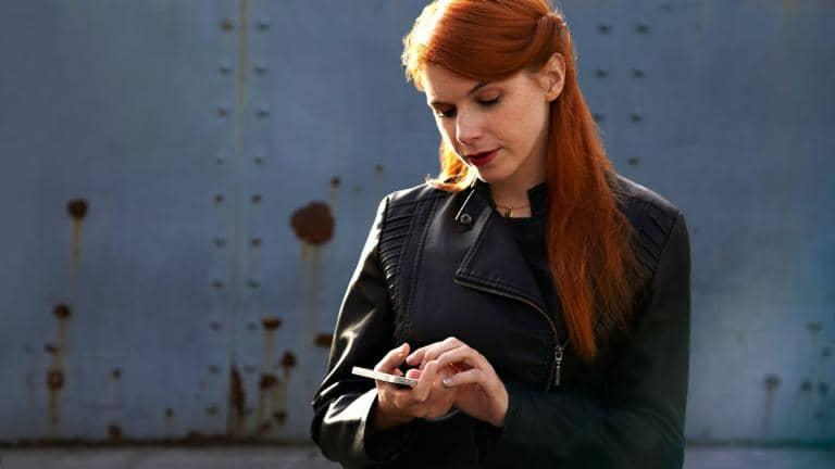 A woman wearing a leather jacket looking at her phone