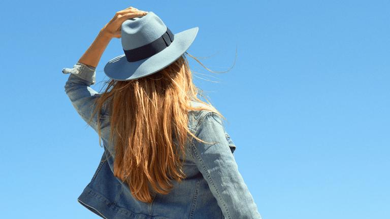 A woman wearing a hat looks up at a clear blue sky