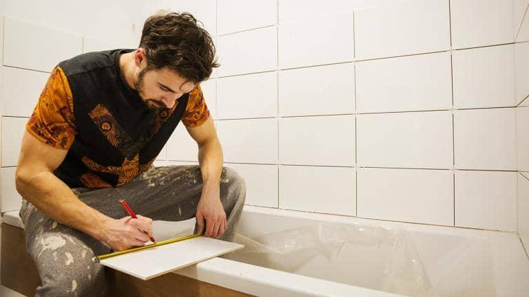 A man tiling his bathroom
