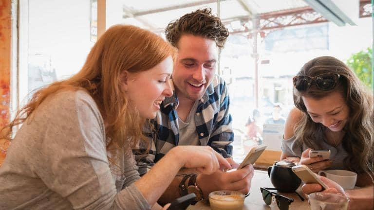 Three friends sitting around a table laughing as they look at their phones