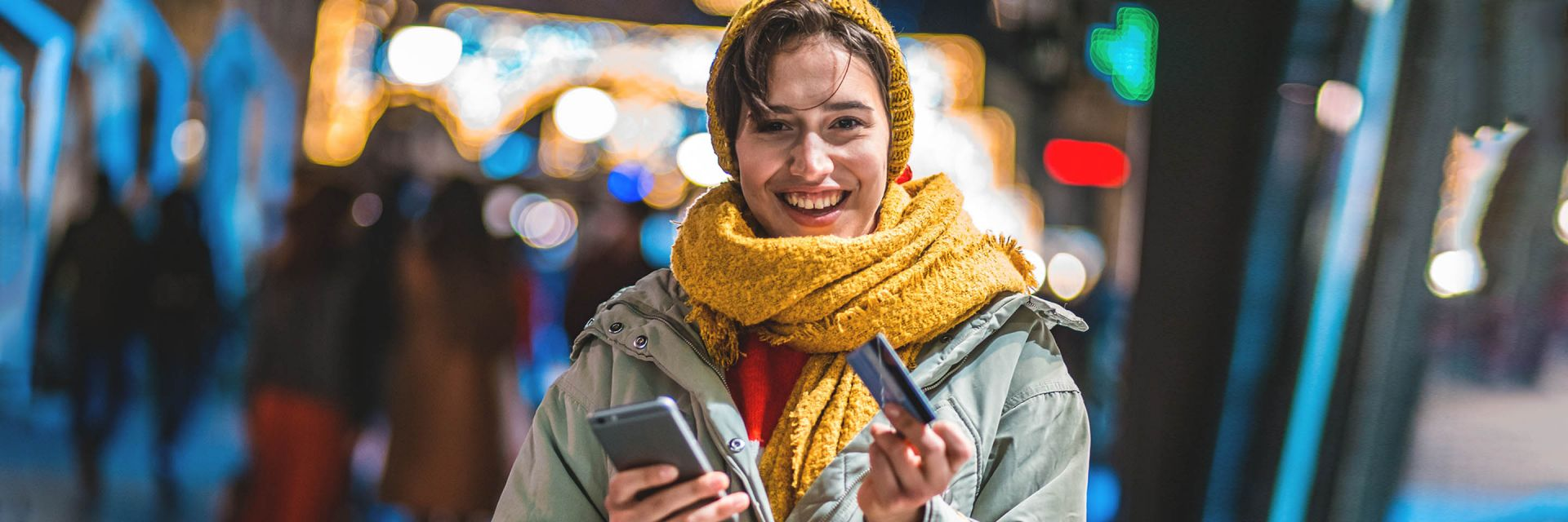 A smiling woman wearing a hat and scarf holds up her smartphone and her bank card