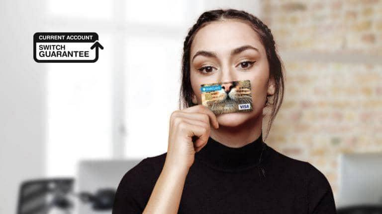 A young woman in a black top holds a bank card to her face covering her nose and mouth