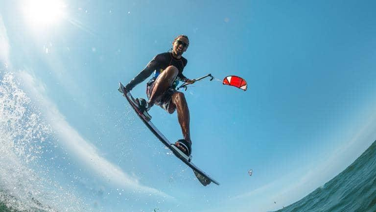 An action shot of a man in mid-air kitesurfing on the ocean