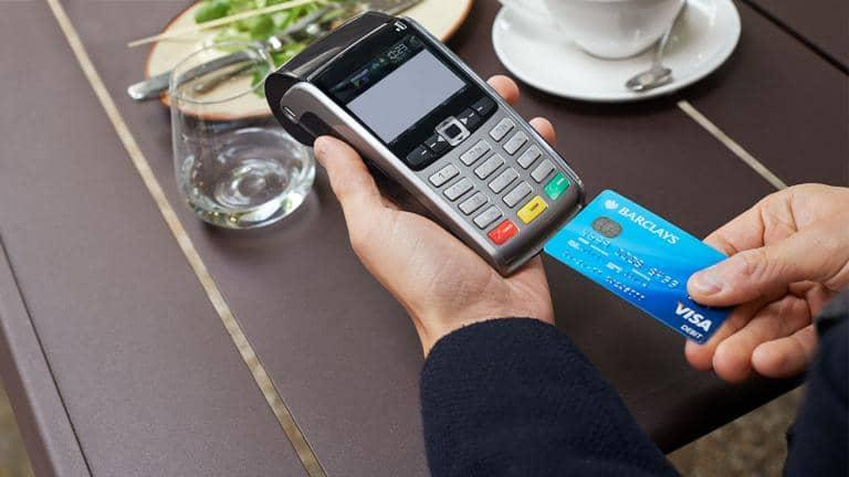 A Barclays Visa Debit card being inserted into a card reader at a restaurant
