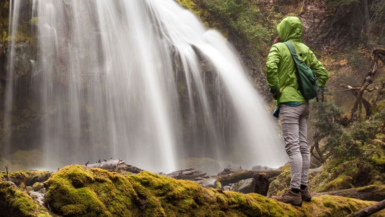 A woman dressed in hiking clothes stands in front of a waterfall in the middle of a forest