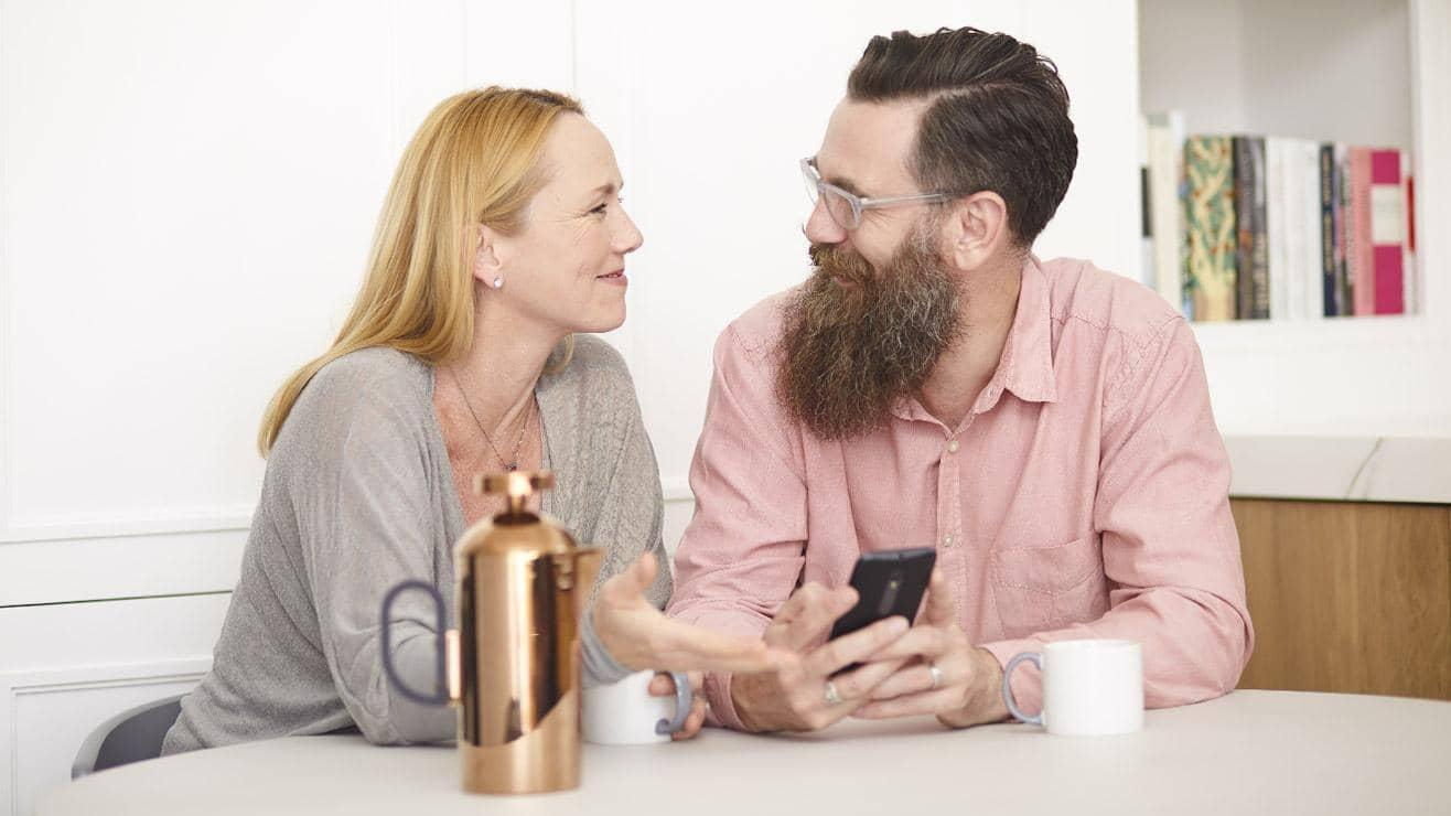 A smiling couple in a kitchen look at a mobile phone and drink coffee