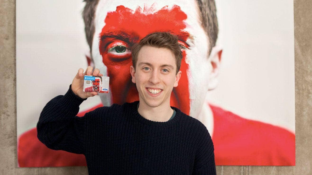 A man holding up a personalised Barclays card in front of a large picture showing the same image
